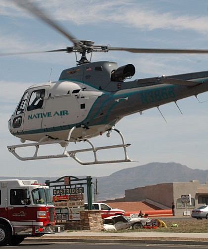 A Native Air helicopter lifts off with the driver of the white car at the bottom of the photo, after an accident at Navajo and 69 on Monday morning.<br>TribPhoto/Heidi Dahms Foster