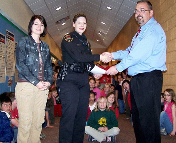 Courtesy Photo<br> Rhett Wagner, Lamb Chevrolet's general sales manager, presents a check to Prescott Valley Police Det. Jennifer Miller and Amy Kidd, fifth grade teacher at Granville Elementary School, on March 7 to ensure the fifth grade DARE graduates could celebrate National DARE Day at Freedom Station in April.