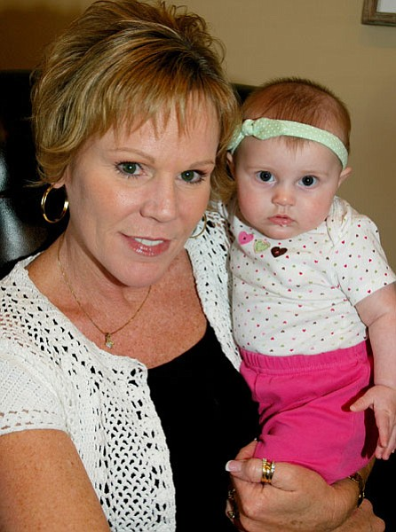 """Trib Photo/Cheryl Hartz<br> Jeri Ann Kooiman cuddles in her Prescott Valley real estate office with the 5-month-old granddaughter, nicknamed """"Hannah Montana"""" that she and husband Dave are raising."""