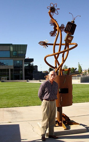 Courtesy Photo/Cynthia Jones<br> Sculptor Rick Hartner stands next to his 12-foot tall piece, In Your Eyes, near the intersection of Lake Valley and Lakeshore roads at the Civic Center. Hartner made this piece entirely from recycled metal.