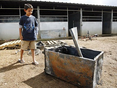 Eight-year-old Bailey Thibeault looks at the small refrigerator that apparently caused a fire in a stall of a barn at Yavapai Downs on Tuesday night. Thibeault, who was on scene when the fire was being put out, said the scariest part for him was when a running horse tried to stop and flipped over a gate. He added that he thought the horse was OK.<br> <i>Courier Photo/Les Stukenberg</i>