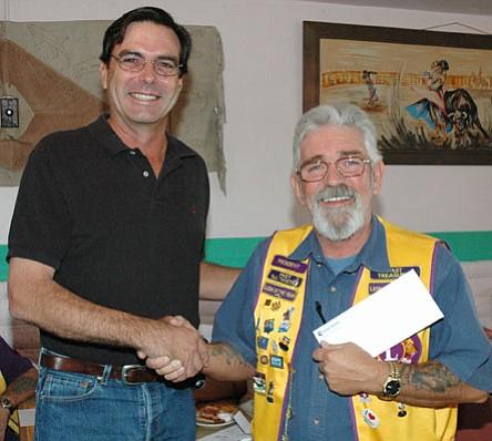 Prescott Valley Early Bird Lions Club President Norm Pariseau accepts a check for $5,068 from Mike Fann, Yavapai County Community Foundation advisory board member, on Sept. 17.<br> <i>Trib Photo/Cheryl Hartz</i>