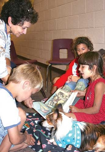 Mountain View Elementary School third grader Djanice Azevedo reads Where the Wild Things Are to Wrigley, a Reading Education Assistance Dog. Also listening in are JoAnn Hayden, special education teacher, Josh Grant, left, and Patricia Azevedo, at rear.<br> <i>TribPhoto/Sue Tone</i>