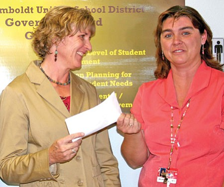 Liberty Traditional School ELL teacher Laurel Wolfinger, left, accepts a FATES grant from FATES President Kristi Goeke. Wolfinger will use the $450 to purchase reading materials and the Readers' Theater program for her students.<br> <i>Trib Photo/Sue Tone</i>