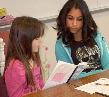 """Katie Alexander, left, reads from a book created by Glassford Hill seventh grader Aliya Gobin (her book was """"If You Take a Bat To Baskin Robbins"""")<br> Courtesy photo"""