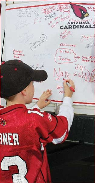 Nate Chinander, wearing a jersey honoring Cardinals quarterback Kurt Warner, writes that he is Warner's biggest fan.<br> Trib Photo/Cheryl Hartz