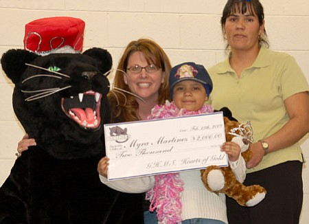 The Glassford Hill Middle School Panther mascot and Principal Kristen Rex, second from left,  deliver a check this past month for $2,000 to Lake Valley Elementary School second grader Mayra Martinez and her mother, Maria, as part of the middle school's Hearts of Gold fundraiser to help with costs for Mayra's chemotherapy treatment.<br> Courtesy Photo