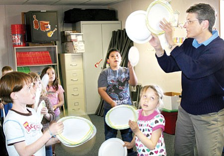 Using paper plates as percussion instruments, Amy Van Winkle, right, leads CSES first graders in a rhythm and movement activity.<br> TribPhoto/Sue Tone