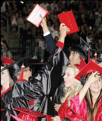 Grads raise their diplomas in celebration at the end of the Bradshaw Mountain High School grad ceremony last Thursday at Tim's Toyota Center.<br> TribPhoto/Cheryl Hartz