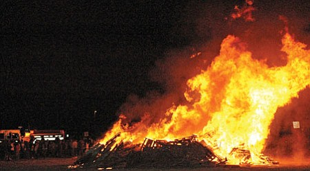 CYFD firefighters start and then keep a close eye on the huge bonfire Thursday night.<br> TribPhotos/Cheryl Hartz