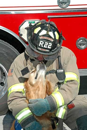 Mayer Firefighter Dave Lattman shares a hug with Buster during training Saturday in Prescott Valley. Lattman helped to familiarize the therapy dogs with firefighters' gear.<br> TribPhoto/Heidi Dahms Foster
