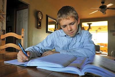 Ryan Rozendaal works on some schoolwork at his home in Prescott Valley Saturday afternoon. Rozendaal recently won a statewide poetry contest for home-schooled students and will read his poem during Home School Day at the state Capitol in Phoenix.<br> Photo courtesy of Matt Hinshaw/The Daily Courier