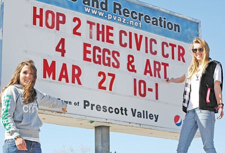 Parks and Recreation employees Erin Casperson, left, and Melissa Ilkay showcase the sign they just finished announcing the Town of Prescott Valley's annual egg hunt, the Eggstravaganza, this Saturday on the Civic Center grounds from 10 a.m. to 1 p.m.<br> Trib Photo/Cheryl Hartz