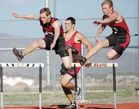 Left to right, Bradshaw Mountain hurdlers Paul Wiser, Chase Sullins and Kevin Wallace nearly come abreast as they round the second curve of the 300-m hurdle race in a dual meet with Prescott this past week in Prescott Valley. Wallace won, Wiser was 2nd and Sullins, 3rd. Trib Photo/Cheryl Hartz