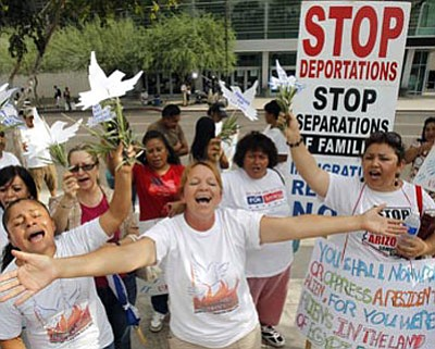 From left to right, Georgina Sanchez, Maria Uribe, and Rosalinda Macias, all of Phoenix, sing as they join dozens to protest the SB1070 Arizona immigration law in front of U.S. District Court  July 22 in Phoenix. A judge Wednesday blocked the most controversial sections of Arizona's new immigration law from taking effect Thursday.<br> Ross D. Franklin/The Associated Press
