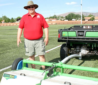Parks and Rec Director Brian Witty runs the Greens Groomer around the artifical turf fields at Mountain Valley Park, where the equipment gathered more than a hundred cigarette butts left behind by attendees at the fireworks show. Tobacco products are not allowed on the field.<br> TribPhoto/Sue Tone