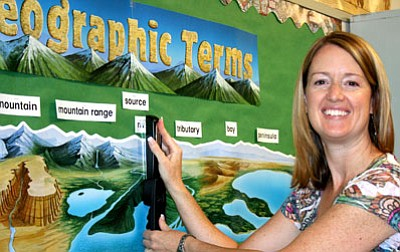 Jennifer Mraz, Lake Valley Elementary School sixth-grade teacher, puts the finishing touches on her bulletin board Monday morning. Mraz said she will use her experience as former Lake Valley and Mountain View librarian to help students with research and technology skills.<br> Trib Photo/Sue Tone