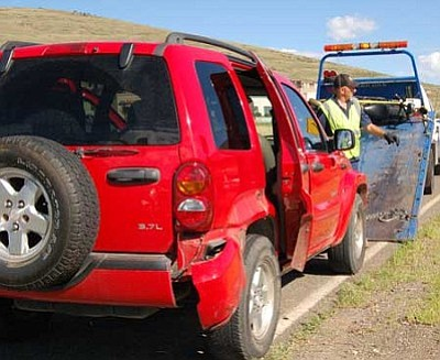 A tow truck driver loads a 2007 Harley Davidson motorcycle and a Jeep Liberty for transport after an early morning accident on Highway 69 that critically injured the cyclist. <br> Photo courtesy Bruce Colbert