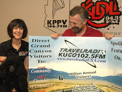 Terry and Sanford Cohen, along with their standard poodle, Diva, display a folding board advertising their newest venture, Travelradio, in front of the logos of Prescott Valley's first radio station, KPPV, and the more recent KDDL.<br> TribPhoto/Cheryl Hartz