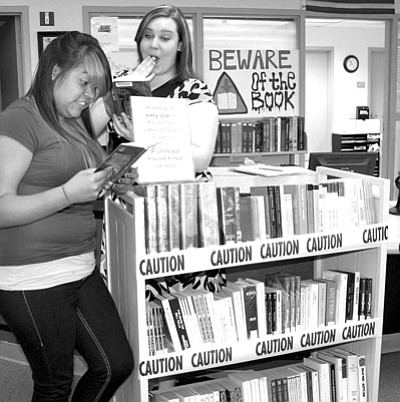 Teacher's Assistant Atalia Hernandez, left, a junior at Bradshaw Mountain High School, and Library Assistant Amanda Hiler find something of interest to read from a cartful of books that appear on high school reading lists. Some adults object to language or content in classics such as The Hobbit or A Separate Peace.<br> Trib Photo/Sue Tone