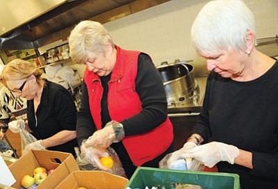 Volunteers Eula Parish, left, Marcy Lage and Judy Lauver pack food in Nov. 2010 for underprivileged PUSD students to take home on weekends. Volunteers will help to implement a similar program in PV.<br> Photo courtesy Brett Soldwedel