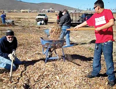 Roberto Ortega, right, and other volunteers ready the Prescott Valley Community Garden by spreading wood chips along the pathways this past Saturday morning.<br> Trib Photo/Sue Tone