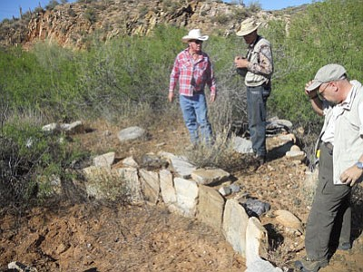 Kevin Leonard, left, president of the Dewey-Humboldt Historical Society, along with members Gerald Hoyer and David Nystrom, check out an arrastra site (where mules pulled a flat stone in a circle to crush ore) near the Vulcan Lode claim on a DHHS field trip to to Blue Bell Mine.<br> Courtesy Photo