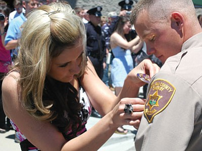 Hailee Scarbrough pins a new badge on husband, Justin Scarbrough, with the Yavapai County Sheriff's Office, following NARTA graduation ceremonies May 12. Former Prescott Valley residents, the couple resides in Chino Valley.<br> Trib Photo/Cheryl Hartz