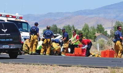 Les Stukenberg/The Daily Courier<br> Emergency personnel treat the victims of a one-vehicle rollover on Glassford Hill between Long Look and Spouse in Prescott Valley Friday afternoon. One person died at the scene and another was airlifted to a hospital.