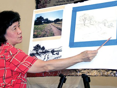 Mei-June Liao describes how she altered a scene of Willow Lake from the photo to a sketch before demonstrating pastels to members of the PV Art Guild on Tuesday.<br> TribPhoto/Sue Tone