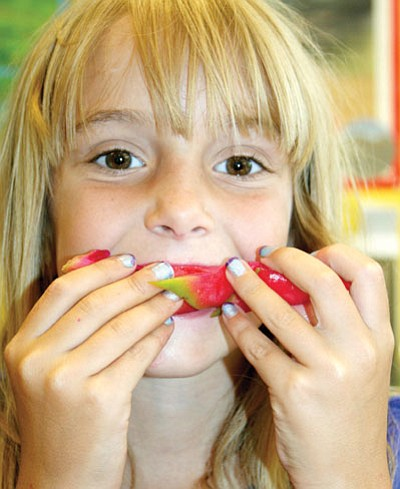 TribPhoto/Sue Tone<br /><br /><!-- 1upcrlf2 -->Third-grader Melody Perkins eats her dragon fruit right off the outer skin at Lake Valley Elem. School.