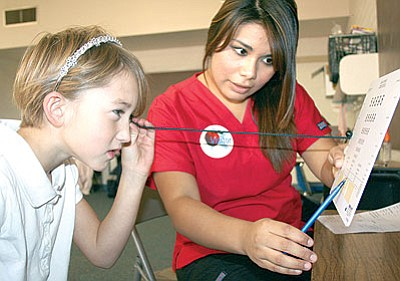Liberty Traditional student Abigail Arnall uses a string to keep the correct distance from the board during her near vision test by Certified Nursing Assistant student Jazmin Segundo, a junior at Bradshaw Mountain High School.<br> Trib Photo/Sue Tone
