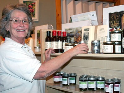Denise Rogers arranges jars of Donya Marie's Dark Chocolate Salsa on the shelves of Dewey-Humboldt's new store, Gifts and Games. She sells local food products, books, games and artwork, in addition to sales and trades of video games and DVDs.<br> TribPhoto/Sue Tone