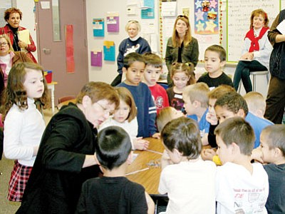 Sue Larson, at the table in black at left, teaches kindergarten students a math game with dice and coins that introduces place value at Lake Valley Elementary School in December. Kindergarten and first-grade teachers from district schools watch and learn how to teach inductive math activities through Larson's workshops.<br> Trib Photo/Sue Tone