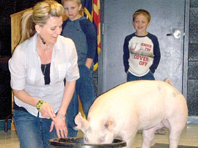 Principal Candice Blakely-Stump with Baby Blue, a pig owned by James and Chance Scott, in background.<br> Courtesy Photo