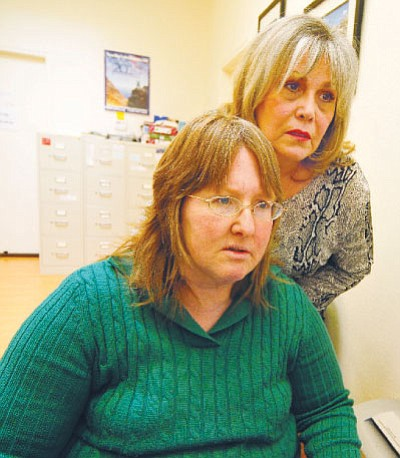 Gail Kenny, left, and Liz Toone, study a computer image at New Horizons in Prescott Valley. Kenny, who helps people access to their available benefits, will be one of 500 people nationwide who will lose their jobs if Congress does not reauthorize the spending that pays for their positions.<br> Photo courtesy Les Stukenberg