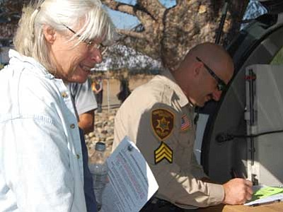 Linda Lombardo, wife of Crown King Fire Chief Steve Lombardo, gets her Yavapai County Sheriff's Office pass Friday to return home.<br> Photo courtesy Joanna Dodder