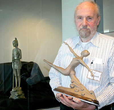 """Roy Leroux holds """"Jete,"""" one of his two bronze sculptures on display on the third floor of the Civic Center. """"Huntress"""" is visible through the glass case at left.<br> Trib Photo/Sue Tone"""