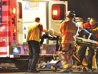 Emergency personnel load a woman injured in a three-vehicle head-on collision Sunday night into an ambulance. Four people were hurt in the crash, and two more refused treatment at the scene.<br> TribPhoto/Heidi Dahms Foster