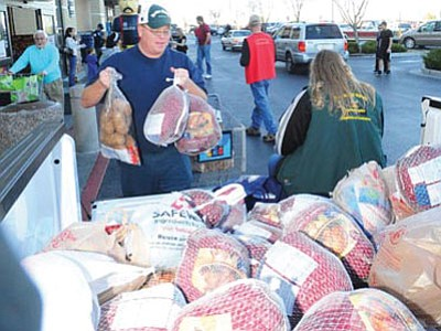 Russ Lorton of Prescott Valley donates two turkeys and a sack of potatoes to the Flying High Turkey Drive at the Prescott Valley Fry's store Monday afternoon.<br> Photo courtesy Les Stukenberg