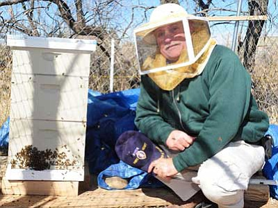 Cliff Deane shows off one of the beehives that he collects honey and wax from near his home in Dewey. Deane says he will remove bee swarms from people's property for free.<br> Photo courtesy Les Stukenberg