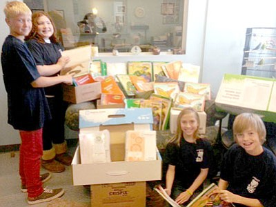 Acorn students pose with books and curriculum materials purchased with grant money. From left are Mack Heitman, sixth grade; Kayleigh Lopez, seventh grade; Paige Herrera, sixth grade; and Bryce Archer, seventh grade.<br> Courtesy Photo