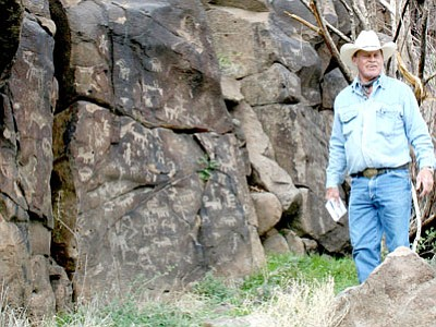 "Kevin Leonard stands next to what he calls a ""story wall"" of spectacular petroglyphs at Perry Mesa in 2010, one of the six-hour tours he plans to offer in the future through his new business, Humboldt Mining Tours. Current shorter trips include a loop drive out Iron King Road with a silver mine guests can explore, the old McCabe Cemetery, and a six-room Indian ruin.<br> Trib File Photo/Sue Tone"