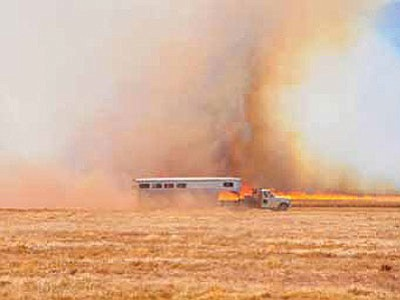 A truck and trailer travel Perkinsville Road past a wildfire that grew to 500 acres Tuesday afternoon.<br> Photo courtesy Matt Santos/Chino Valley Review