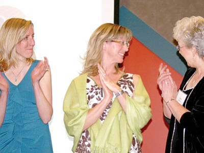 Bonny Smith, center, receives congratulations from Penny Nicholas, right, and Laura Russo as Smith is announced as the 2013 Yavapai County Teacher of the Year at Friday's award ceremony at the Prescott Resort. BMHS's Russo was chosen tops in the Cross Grades category.<br> TribPhoto/Sue Tone