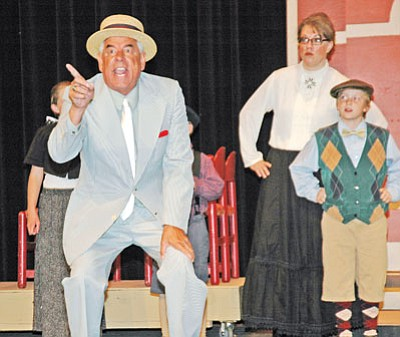 """Professor Harold Hill (Brian Martinez) expounds on the evils of a new pool table to the townsfolk of mythical River City, Iowa, during dress rehearsal for the Lonesome Valley Playhouse production of Meredith Wilson's """"Music Man."""" Directed by Clyde Neville, with assistant director Tamee Niekamp, musical director Shana Burton, accompanist Jackson Rauch, choreographer Alexes Niekamp and mentor Brooke Williams.<br> TribPhoto/Cheryl Hartz"""