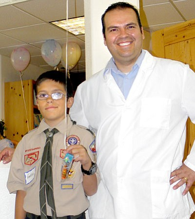 Ammon Montes, 11, poses with his father, Dr. Sergio Montes, June 28 while helping out during the business' Project Smile event.<br> Courtesy Photo
