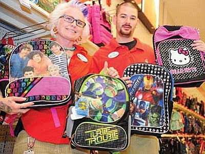 Target team members Jamie Pfeifer and Adam Puertas show off some of the best-selling backpacks for the retailer in the Frontier Village Shopping Center.<br> Photo courtesy Les Stukenberg/The Daily Courier