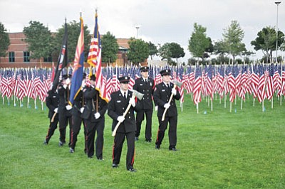 The Central Yavapai Fire District Honor Guard enters Prescott Valley's 9/11 observance in Sept. 2012, with the backdrop of 1,000 American flags on the newly opened Healing Field. This year, 3,000 flags will fill the space between the Civic Center and police department.<br> TribFile/Heidi Dahms Foster