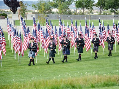 Members of the Veterans Memorial Piper Corps lead the way into the opening ceremony among the 3,000 American flags of the Healing Field at the Prescott Valley Civic Center Saturday. The event included remarks by Mayer Harvey Skoog, Prescott Valley Councilwoman and Healing Field visionary Mary Mallory, and Arizona Highlands Piping Society Director J'aime Morgaine, a piping tribute, reading of the Hotshot Prayer by Deborah Phingston, mother of fallen Hotshot Andrew Ashcraft, and a blessing of the Healing Field by Scottish American Military Society Chaplain Larry Kimmel. The Healing Field will remain open through this week.<br> TribPhoto/Heidi Dahms Foster